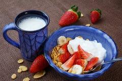 Sund frukostcornflakes, nya jordgubbar, banan, yogur Arkivbilder