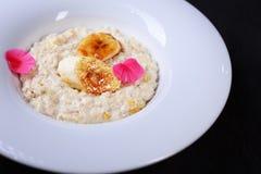 Sund frukosthavremjölhavregröt med bananer royaltyfria bilder