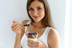 Sund frukostkvinna med exponeringsglas av yoghurt, bär och havre royaltyfri bild
