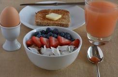 Sund frukostplats med grapefruitefruktsaft, det kokta ägget, spirat kornrostat bröd och stålsnitthavremjölet med frukt arkivbilder