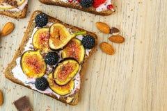 Sund frukostskiva av wholegrain rostat bröd med gräddost, fikonträd, muttrar och Blackberry Top beskådar royaltyfri foto