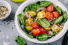Sund grön bunkesallad med spenat, quinoa, gula och röda tomater, lökar och frö Royaltyfri Foto