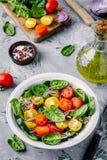 Sund grön bunkesallad med spenat, quinoa, gula och röda tomater, lökar och frö Arkivbild