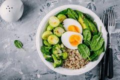 Sund grön lunch för den vegetarianbuddha bunken med ägg, quinoaen, spenat, avokado, grillade brussels groddar och broccoli på mör royaltyfria bilder