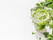 Sund grön smoothiedrink i exponeringsglas med grönkålingredienser på vit träbakgrund, slut upp royaltyfri foto