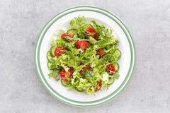 Sund grönsaksallad av den nya tomaten, gurkan, spenat, frize och sesam på plattan Banta menyn arkivfoto