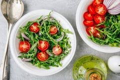 Sund gr?n ny Arugulasalladbunke med tomater och r?da l?kar Top besk?dar fotografering för bildbyråer