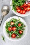 Sund gr?n ny Arugulasalladbunke med tomater och r?da l?kar Top besk?dar arkivbild