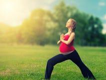 Sund gravid kvinna som gör yoga i natur