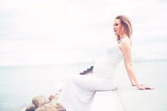 Sund gravid kvinna som kopplar av på sjösidan Arkivfoton