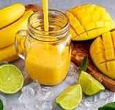 Sund gul bananmangoSmoothie med skivor av limefrukt, mintkaramellen och is Royaltyfria Foton
