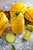 Sund gul bananmangoSmoothie med skivor av limefrukt, mintkaramellen och is Royaltyfri Bild