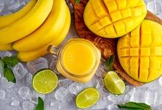 Sund gul bananmangoSmoothie med skivor av limefrukt, mintkaramellen och is Royaltyfri Foto
