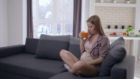 Sund havandeskap, den lyckliga moderskapkvinnan med den stora magen dricker fruktsaft för ny frukt och tar omsorg av framtida bar lager videofilmer