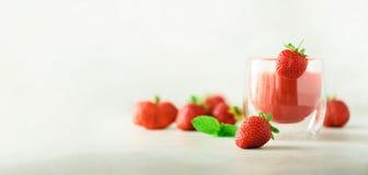 Sund jordgubbesmoothie i exponeringsglas på grå bakgrund med kopieringsutrymme baner Sommarmat och rengöring som äter begrepp arkivfoto