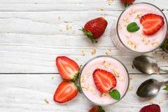 Sund jordgubbeyoghurt med havre och mintkaramellen i exponeringsglas med nya bär och skedar över den vita trätabellen Arkivbild