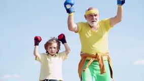 Sund kämpefarfar och sonson med boxninghandskar Farfar och sonson som gör boxas utbildning i morgon stock video