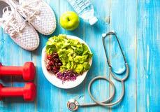 Sund kondition för livsstilsportutrustning, gymnastikskor, grönt äpple, sötvatten och sund mat på blå wood bakgrund royaltyfria bilder