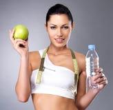 Sund kvinna med äpplet och flaskan av vatten Arkivbild