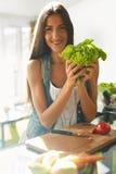 Sund kvinna som äter grönsaker i kök Viktförlust bantar royaltyfria bilder