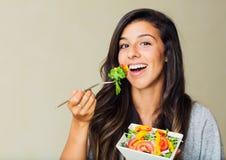 Sund kvinna som äter sallad arkivfoton