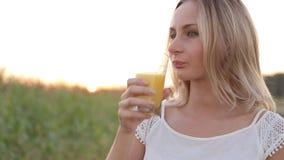 Sund kvinna som dricker orange fruktsaft och att le lager videofilmer