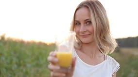 Sund kvinna som dricker orange fruktsaft och att le arkivfilmer