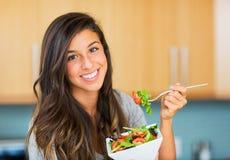 Sund kvinna som äter sallad Arkivbilder