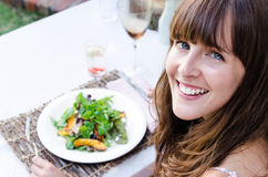 Sund kvinna som utomhus äter sallad arkivbild