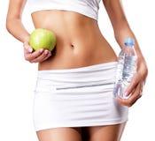 Sund kvinnlig kropp med äpplet och vatten Arkivfoton