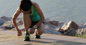Sund löpare för livsstilkonditionkvinna som binder skosnöret, innan att köra på den soliga sjösidan stock video