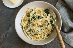 Sund lantlig pastamaträtt med spenat, mandeln och parmesan arkivbilder