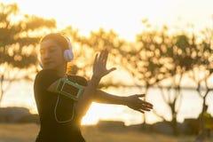 Sund le kvinna som värmer upp sträcka hennes armar i aftontiden, solnedgång Royaltyfri Fotografi