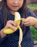 Sund liten flicka som äter bananen Den lyckliga ungen tycker om att äta ny frukt Arkivfoto