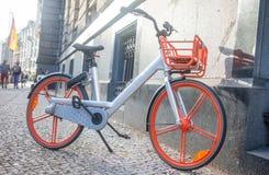 sund livsstil för begrepp Cykeln med grå och orange färg är parkerat utomhus- Gör suddig byggnadsbakgrund arkivbild