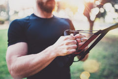 sund livsstil för begrepp Den muskulösa idrottsman nen som övar trx, skjuter utanför i soligt parkerar upp Färdig shirtless manli royaltyfri bild