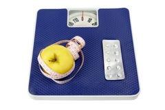 sund livsstil för begrepp På vågen ligg: å ena sidan ett äpple och ett mäta band, å andra sidan en medicin royaltyfri fotografi