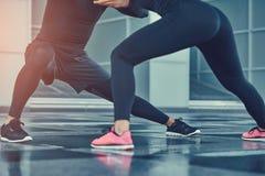 sund livsstil för begrepp Unga konditionpar i en sportswear, göra utfall i den moderna staden mot en skyskrapa Arkivbilder