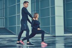 sund livsstil för begrepp Unga konditionpar i en sportswear, göra utfall i den moderna staden mot en skyskrapa Royaltyfria Bilder
