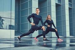 sund livsstil för begrepp Unga konditionpar i en sportswear, göra utfall i den moderna staden mot en skyskrapa Arkivbild