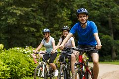 Sund livsstil - folket som rider cyklar i stad, parkerar Arkivbilder