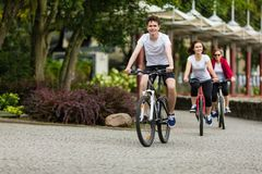 Sund livsstil - folket som rider cyklar i stad, parkerar royaltyfria foton