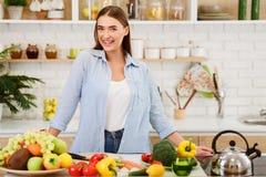Sund livsstil Kvinna som ser kameran i kök royaltyfri foto