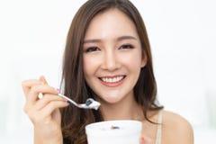 Sund livsstil Le den lyckliga unga asiatiska kvinnan som ?ter med f arkivfoton
