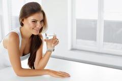 Sund livsstil Lycklig kvinna med exponeringsglas av vatten drinkar läka arkivfoto