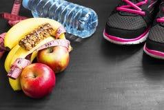 Sund livsstil med sportobjekt, frukter och vatten royaltyfria bilder