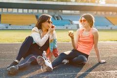 Sund livsstil och sunt matbegrepp Le konditionmodern och den tonåriga dottern som äter tillsammans äpplesammanträde på stadion arkivfoto