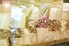 Sund livsstil, rengöring och naturlig mat Muttrar - russin, jordnötter, hasselnötter packat i pappers- påsar, ställning på räknar arkivfoto