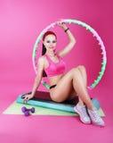 Sund livsstil Sportigt kvinnasammanträde på mattt med konditionutrustning royaltyfri foto