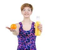 Sund livsstil, sunt äta Ung flicka med en flaska av orange fruktsaft och apelsinen som ler, på en vit isolerad bakgrund H arkivbilder
